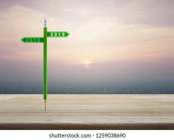 2019 and 2018 direction sign plate with green pencil on wooden table over modern office city tower and skyscraper, vintage style, Business happy new year planning concept
