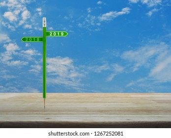 2019 and 2018 direction sign plate with green pencil on wooden table over blue sky with white clouds, Business happy new year planning concept