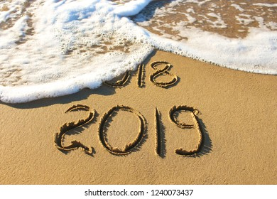 2019, 2018 years written on sandy beach sea. Wave washes away 2018.