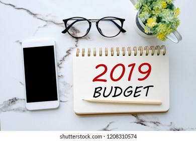 2019 budget word on notebook paper background and smart phone on white marble background, financial concept, business strategy