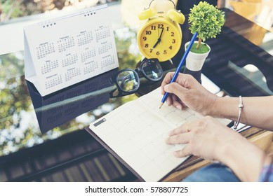 2019 Calendar planner agenda plan on  schedule event. Timetable agenda of wedding organizing timetable by organizer schedule. Woman hands writing agenda on calendar desk. Calendar event plan concept
