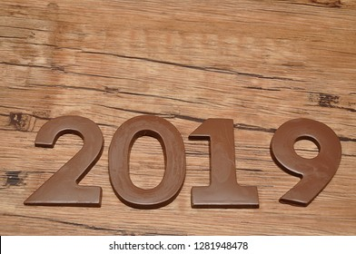 2019 in chocolate figures against a wooden background