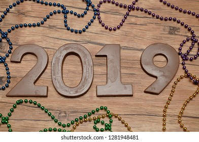 2019 in chocolate figures against a wooden background with colorful strings of beads
