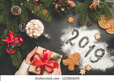 2019 Christmas or New Year background with gift box, fir tree, hot chocolate. 2019 written on flour on black concrete background. Festive Winter Holidays concept