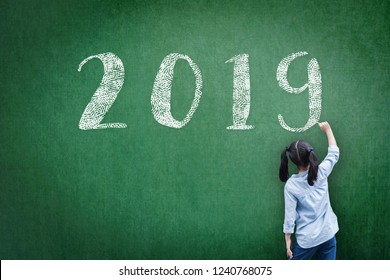 2019 class new calendar year greeting by student kid's hand drawing on school teacher's chalkboard for academic year greeting, educational celebration, classroom schedule concept