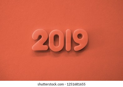 2019 color design trend. Plastic numbers 2019 symbol new year coming on living coral background. Simple design minimalist. Winter holiday poster. New year concept. Plain design end elementary style.