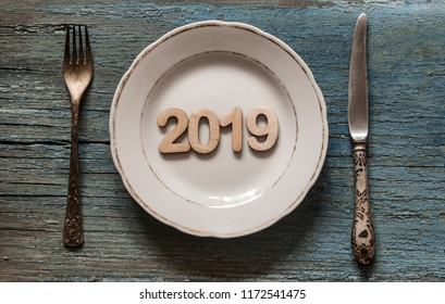 2019 concept on empty plate, fork and knife on wooden tabletop