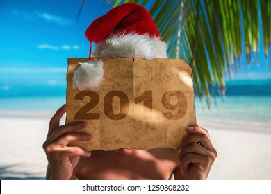 2019 concept. Tourist man with Santa Claus hat relaxing on tropical island beach. Punta Cana, Dominican Republic.