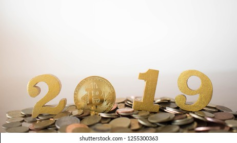 2019 Cryptocurrency financial concept. Golden bitcoin and number 2019 on pile of coin. Copy space.