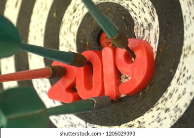 2019 darts target. Darts board with 2019 plastic numbers struck by arrow. Right in target. 2019 achievement. New year goal and resolution.