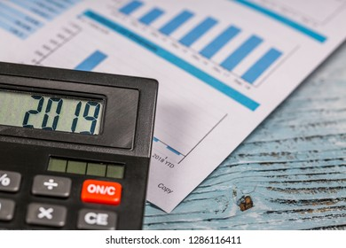 2019 digits on calculator and business document are on the wooden table