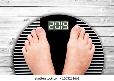 2019 feet on a weight scale on white wooden planks background