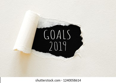 2019 goals list written over torn paper on black background