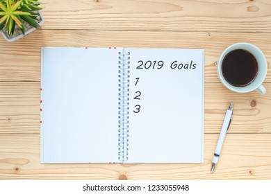 2019 Goals with notebook, black coffee cup, pen and glasses on table, Top view and copy space. New Year New Start, Resolutions, Solution, Strategy and Mission concept