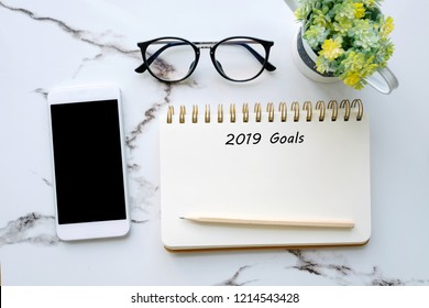 2019 goals on blank note paper background and smartphone with balnk on screen background, new year aim to success in business background