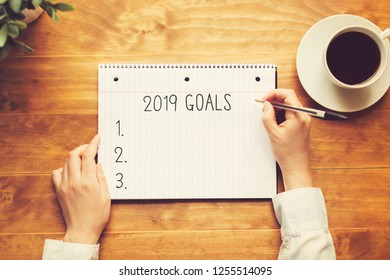 2019 goals with a person holding a pen on a wooden desk