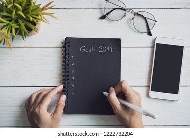 2019 goals text on notebook with smartphone on white wooden desk, New years resolution concept