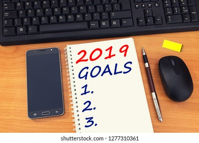 2019 goals text on notebook with office accessories, mobile phone and keyboard. Business plan, direction concept.
