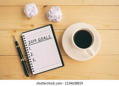 2019 goals text on notepad with coffee, pen and crumpled paper.