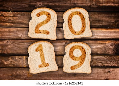 2019 greeting card toasted slices of bread on wooden planks background