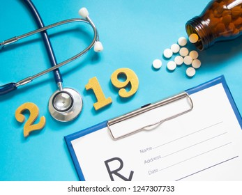 2019 Happy New Year banner for health care and medical concept. Stethoscope w/ doctor order chart, prescription, medicine bottle and gold wooden number 2019 on table blue background. Top view.