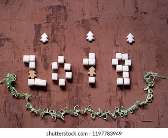 2019 Happy New Year, festive background with the number of the year from pieces of sugar on a dark brown background. Top view.