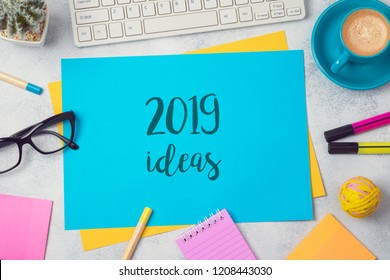 2019 ideas text on colorful paper memo note with business office accessories. Top view from above