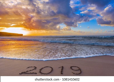 2019 inscription on wet beach sand and a dramatic sky.