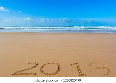 2019 inscription written in the wet yellow beach sand. Concept of celebrating the New Year.