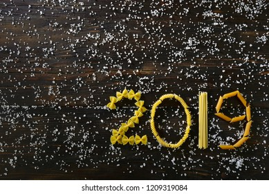 2019 of Italian pasta on a wooden background with salt
