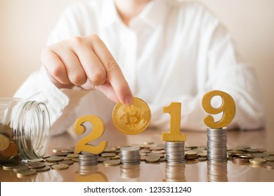 2019 New Digital Money. Female hands putting golden bitcoin with 2019 number on stack of coins. Creative idea for cryptocurrency trading, electronic banking and virtual currency wallet concept.