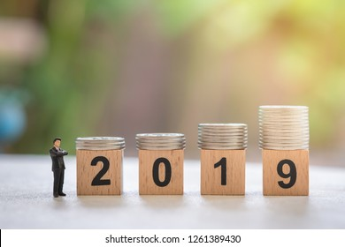2019 New year, Business planning and saving concept. Close up of businessman miniature figure standing and looking to  stack of silver coins on number wooden block.