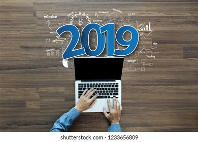 2019 new year business success, Creative thinking drawing charts and graphs strategy plan ideas wooden table background, Inspiration concept with businessman working on laptop computer PC, Top View