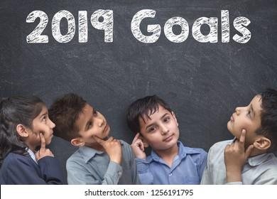 2019  new year concept, Kids standing thinking near blackboard with 2019 Goals drawn over it
