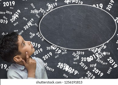2019  new year concept, Young boy`s standing thinking near blackboard with 2019 writtten all over it