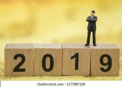 2019 New Year planning and Business concept. Businessman miniature figures standing on wooden number blocks with world map as background.