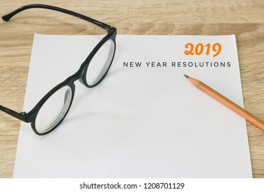 2019 New year resolution note with glasses and pencil on paper and wood table
