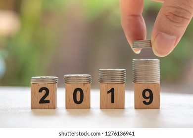 2019 New year and saving concept. Close up of stack of silver coins on number wooden block with man hand holding and put stack of coin on top of stack