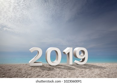 2019 number in 3D on idyllic beach and turquoise water and white clouds in background. Concept of upcoming new year and passing of time.