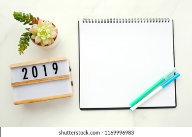2019 on wood box, blank notebook paper on white marble table background, 2019 new year mock up, template with copy space for text, top view