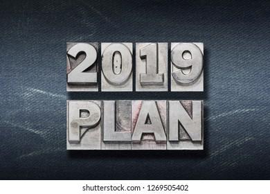 2019 plan phrase made from metallic letterpress on dark jeans background
