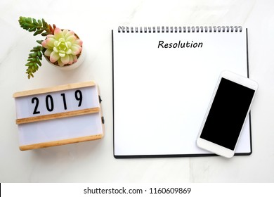 2019 resolution on blank notebook paper, smart phone with blank screen on white marble background, 2019 new year mock up, template, flat lay