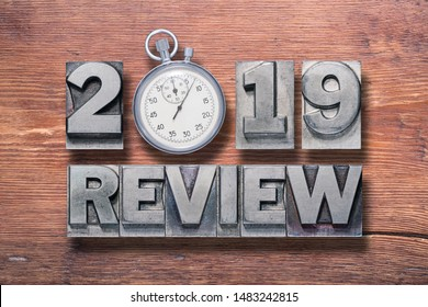 2019 review phrase combined on vintage varnished wooden surface with stopwatch inside