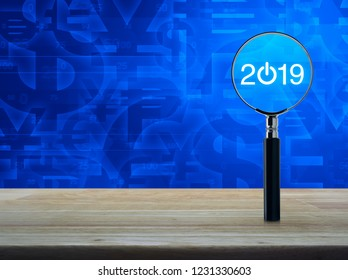 2019 start up flat icon with magnifying glass on wooden table over currency symbol blue tone background, Business happy new year 2019 concept