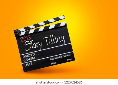 2019 story telling ,text title on movie Clapper board on orange colour backgrounds