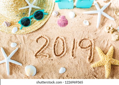 2019 text in the sand with beach accessories
