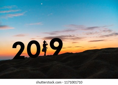 2019 travel concept.Silhouette travel people standing on the beach with 2019 text.