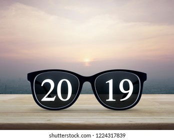2019 white text with black eye glasses on wooden table over city tower and skyscraper at sunset, vintage style, Business vision happy new year 2019 concept