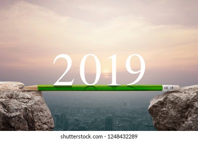 2019 white text with green pencil on rock mountain over aerial view of cityscape at sunset, vintage style, Business success strategy planning concept, Happy new year 2019 calendar cover