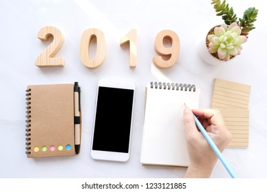 2019 wood letters, hand writing on blank notebook paper, white smart phone with blank screen on white marble table background, 2019 new year mock up, template with copy space for text, top view